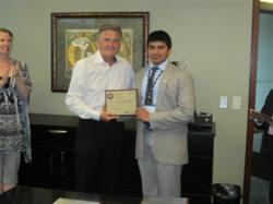 Picture of Prakrit being presented with a plaque by President of WSI