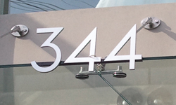 Modern house numbers on store front in brushed aluminum