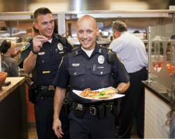 "Geneva Police Officer Chuck Parisi carries a gourmet burger to customers at Tom & Eddie's in Geneva during a fundraiser for Special Olympics Illinois titled ""Burgers & Badges."""