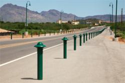 A row of green bollards by Reliance Foundry is displayed at the side of a roadway on the Arizona flood plains.