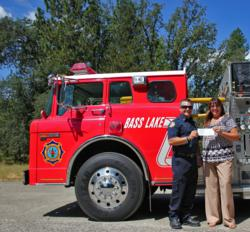 Jordan Owen, a Captain with the Bass Lake Volunteer Fire Department, accepts a check for nearly $600 from Rhonda Salisbury with the Yosemite Sierra Visitors Bureau