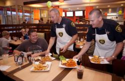 Peter Lamberti, left gets a special delivery from Vernon Hills officers Jim Koch and Bob Lynch at Tom & Eddie's Saturday, Sept.1, 2012, in Vernon Hills, Ill. Uniformed officers from the Vernon Hills Police Department served customers at Tom & Eddie's duri
