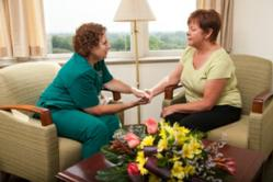 A member of the Midwest CareCenter Hospice Suite at NCH speaks with a family member in the family lounge.