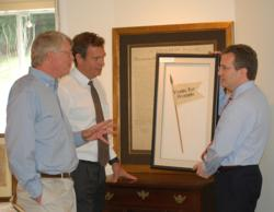 Stephen Desloge (left), John Reznikoff and Seth Kaller (right) discuss placement of various items in the Rockwell Art and Framing Gallery.