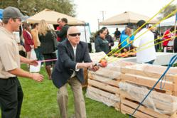 Photo by Nancy Robbins: Brian Davis of Twin Pomegranates Winery looks on as a festival-goer attempts a shot on the popular Pomegranate Grenade launcher at last year's Pomegranate Festival