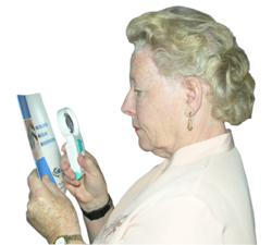 A lady reading a Macular Degeneration leaflet with a Magnifying Glass
