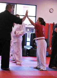 Instructor Bill Munger celebrating with a student at Sandoval Freestyle Karate