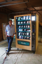 Momba Founder & CEO Steven Duque stands next to one of Momba's customized vending machines, which he currently retrofits in the garage of his and his wife's Newbury, Massachusetts home.