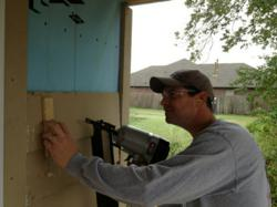 Kyle Burchart, Director of Business Development for Conexus, carefully places siding on a Habitat for Humanity home in Tulsa.