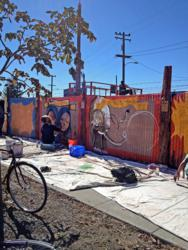 Talented local mural artists have transformed the long fence facing Mandela Parkway into a vibrant, interactive perimeter.  Photo: Marcus Guillard, One Hat One Hand.
