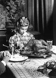 This is a Business Greeting Card with an image of a girl looking at a turkey at thanksgiving dinner.