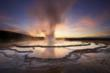Backlit against a painted sky, Yellowstone's Great Fountain Geyser shoots above the terraced reflective pools around its vent, Wyoming, 2008 (© Michael Melford/National Geographic Stock)