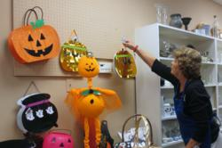 Assistance League Thrift Shop Volunteer with Halloween Merchandise