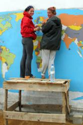 High school students paint a mural in a small community.