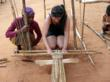 High school student learns to weave with a local Malagasy women.