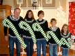 Picture of family wearing funny matching Christmas sweaters for their holiday card
