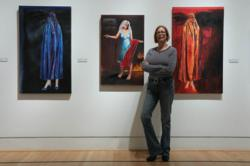 Susan Kraft stands near three pieces of her LET THEM EAT CAKE series in the Splintered Humanity Triton Museum of Art show in Santa Clara, CA
