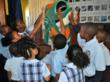 Scholarship recipient students at St. Peter Claver Catholic School enjoy meeting the GEICO Gecko.