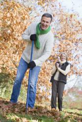Senior couple raking leaves properly to avoid back pain