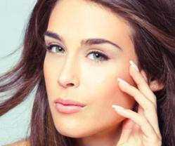 Brunette female caressing her face following Dermapen® skin therapy treatment