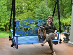"Becky Irvine, and Dozzer, relax on ""Don't Be Koi,""one of her new metal Weather...Or Not™ swings, which has a patent pending on its unique design.  The swing back can be tilted back and forth or be lifted out so the bench can be used as a bed."