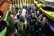 This image is of the staff of Rutabaga Paddlesports next a selection of sea kayaks as they are displayed in Rutabaga's  kayak shop/