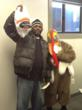 A proud parent of Chester Community Charter School holds up a turkey, while CCCS' Thanksgiving mascot, Chester C. Turkey, distributed $10 gift certificates to Sam & Sam Meats, at the school's recent T