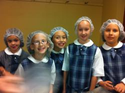 Katie Peters, Rachel Yep, Kasia Takla, Kasia Pytel, and Victoria Legas don their hairnets before handling food for the hungry.