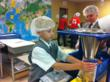 Everest Academy third graders weigh and measure food for starving children.