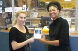 June Middleton, Director of the Church of Scientology Community Center of South Los Angeles (right), presents copies of Truth about Drugs booklets in English and Spanish to a local business for distribution for customers.