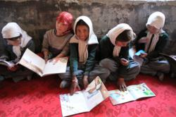 Children at Youl Turtuk Government Primary School excitedly read their new books.