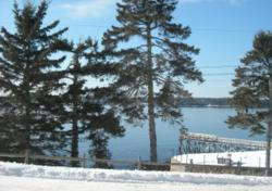 The snow-covered dock and spruces at Spruce Point Inn.