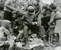 An American GI serving in Italy in World War II is the center of attention as he opens a Christmas box from home. NATIONAL ARCHIVES