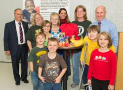 Dr. John Bennett, president & CEO of CDPHP, left, and Mark Quandt, executive director of the Regional Food Bank of Northeastern New York, right, kicked off the 12th annual CDPHP Holiday Appeal to benefit the Food Bank's BackPack Program. They were joined by BackPack Program participants Lauren Charlebois, center (in blue), and her five grandchildren along with representatives from Heatly School in Green Island, from left, Karin Thuber, Lynn Fraim and Kendell Hardy.
