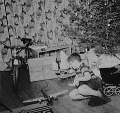 In this Library of Congress image from the AMERICA IN WWII Christmas video, a Virginia boy plays with his new toys--including a toy B-25 bomber--under the Christmas tree in 1941.