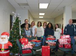 State Collection Service employees gather around presents they purchased for one of their adopted families