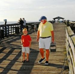 Fishing in Myrtle Beach. Grand dad share the seas, sun and an occasional tug on the fishing line.