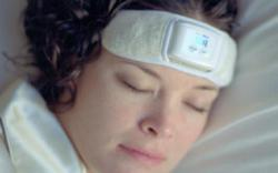 Woman reducing teeth grinding and preventing migraines by using biofeedback headband in sleep