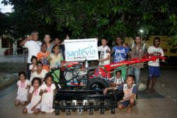 Members of the Roslin Orphanage in West Timor, Indonesia gather around the rototiller plow purchased with funds donated by Santevia Water Systems.