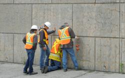 Engineers assessing a Rhode Island concrete wall affected by map-pattern cracking, a symptom typical of alkali-silica reactivity (ASR).