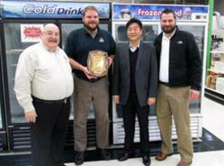 Andrew Kim, from Turbo Air presents the ACityDiscount Restaurant Equipment team with the 2012 Dealer of the Year Award.