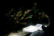Children read the Koran by flashlight at a mosque in Wantugu, Northern Region, Ghana © Peter DiCampo 2007