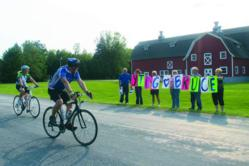 Cyclist rides past supporters at a fundraising bike event