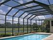 A screened pool enclosure from Venetian Builders, Inc., Miami, keeps out pests and even errant golf balls but preserves views, ventilation and sunlight.