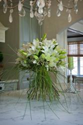 European hand-tied bouquet with Oriental lilies, wax flower and bear grass.