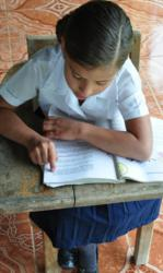 Priscella reads from one of the school's textbooks. It's her turn to take home a book that is shared by the other students in her grade.