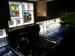 Glass tile blocks in a dramatic light filled kitchen backsplash project