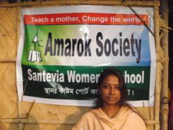 A mother and student stands in front of a sign declaring the opening of the new Amarok Society mother's school