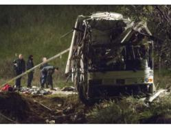 investigators search through bus crash wreckage for clues to accident.