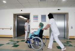 a nursing home patient is wheeled by an aid.